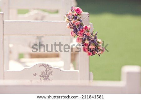 Wedding ceremony chairs and a wreath of roses  - stock photo