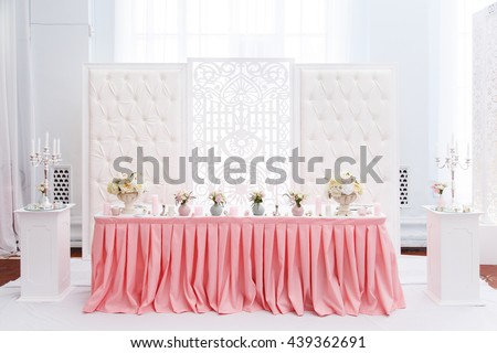 Wedding ceremony decoration in the restaurant. Decoration of wedding table with tender pink textile - stock photo