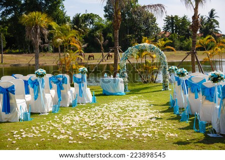 wedding ceremony flowers, arch, chairs - stock photo