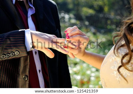 Wedding ceremony moment where the bride places the wedding ring on the groom finger - stock photo
