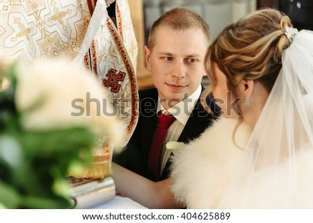 wedding ceremony of happy elegant blonde bride and stylish groom, holding hands on bible and taking vows in the old church - stock photo