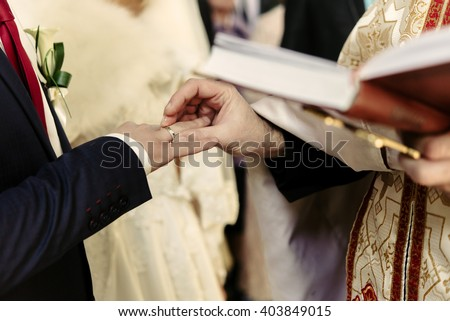 wedding ceremony of stylish elegant blonde bride and happy groom, putting on rings  in the old church - stock photo