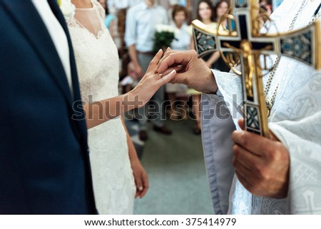 wedding ceremony of stylish elegant bride and groom in the church, exchange wedding rings - stock photo
