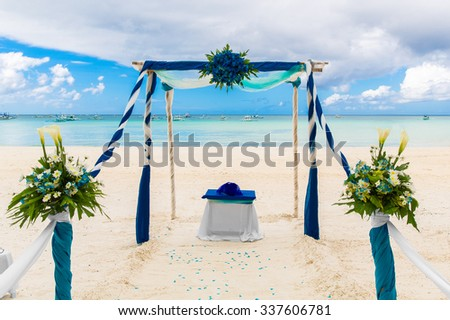Wedding ceremony on a tropical beach in blue. Arch decorated with flowers on the sandy beach. Wedding and honeymoon concept. - stock photo