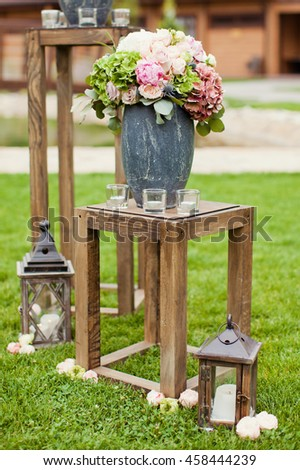 wedding ceremony with flower compositions on wooden stand - stock photo