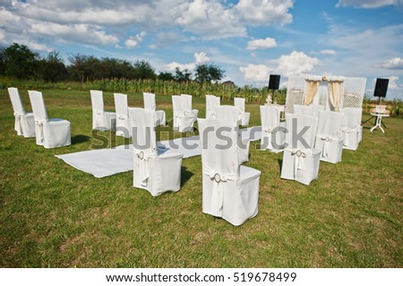 Wedding chair, white carpet with small table on white and golden tones on wedding ceremony.