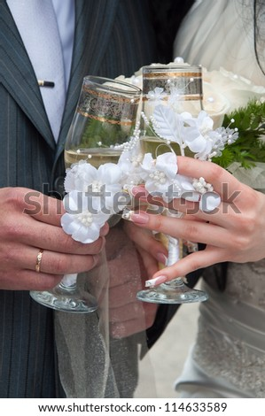 Wedding champagne in hands of the groom and the bride against a bouquet