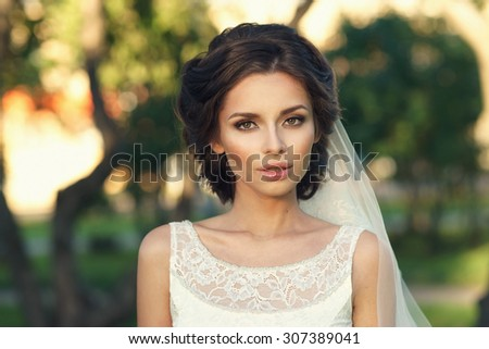 Wedding. Closeup portrait of young beautiful bride in white dress and veil looking at you - stock photo