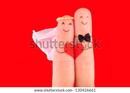 wedding concept - newlyweds painted at fingers against red background - stock photo