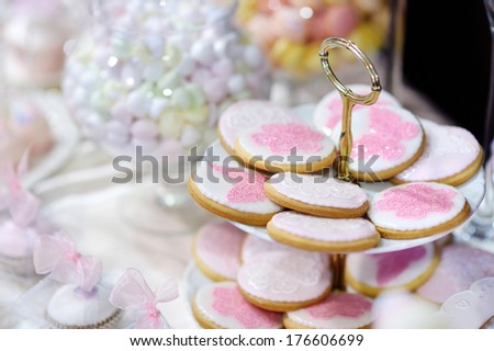 Wedding cookies decorated with pink flowers and butterflies - stock photo
