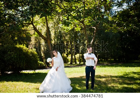 Wedding couple at park near trees and bushes