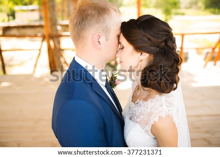 Wedding couple. Beautiful bride and groom. Just married. Close up. Happy bride and groom on their wedding hugging. Groom and Bride in a park. wedding dress. - stock photo