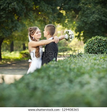 wedding couple, beautiful young bride and groom standing in a park outdoors holding hands and smiling - stock photo
