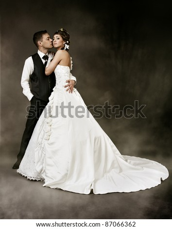 Wedding Couple, Bride and Groom fashion portrait, over dark background. - stock photo