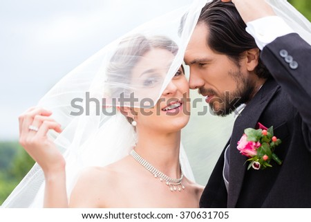 Wedding couple bride and groom hiding under veil - stock photo