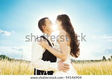 Wedding couple bride and groom in nature. sun shine through kiss - stock photo