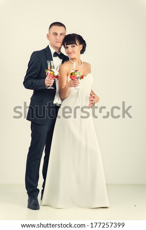 Wedding couple. Bride and groom portrait in studio isolated on white background. Happy holiday of new family. Wedding bouquet of flowers and bridal dress. Cute young married couple