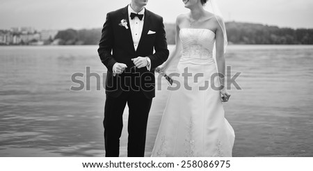Wedding couple dancing by the lake. Newlyweds just having fun. - stock photo