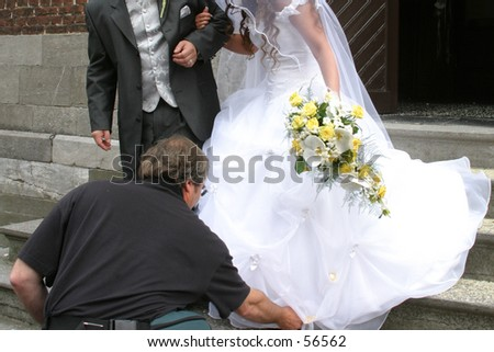 wedding couple descending the church stairs with help of the photographer - stock photo