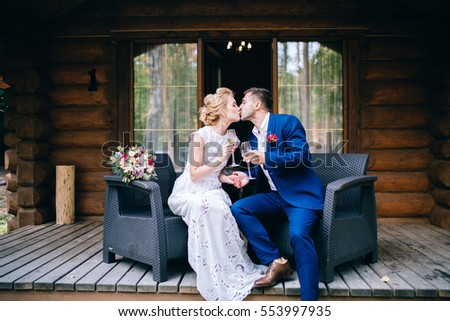 Wedding couple drink champagne near the wooden house