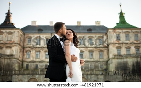 Wedding couple enjoys the sunset over the old castle