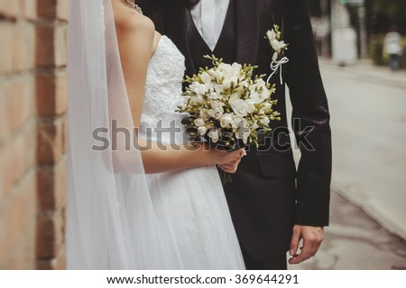 Wedding couple. Groom and bride embracing next to red brick wall. Hands of newlyweds  together.