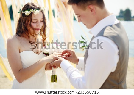 Wedding couple. Groom putting a wedding ring on bride's finger. - stock photo
