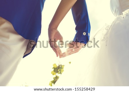 wedding couple hands touching fingers in the shape of hearts. Bright light of the sun on background. - stock photo