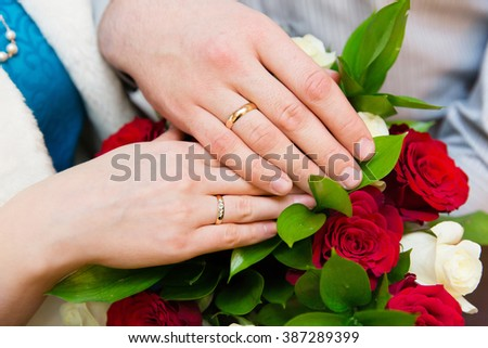 Wedding couple hands with wedding rings on bride's bouquet