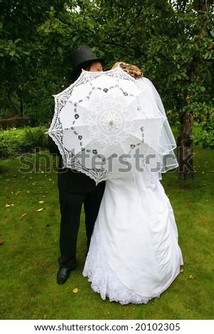 Wedding couple hiding behind the umbrella - stock photo