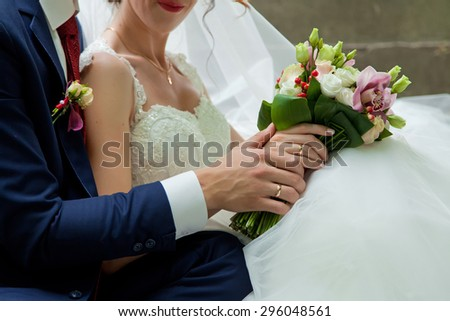 Wedding couple holding bouquet in nature