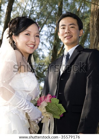 Wedding couple holding flower bouquet smiling in the golf course
