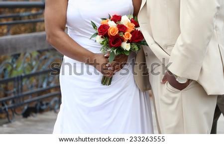 wedding couple holding flowers outdoors - stock photo