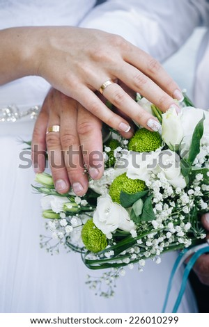 Wedding couple holding hands on bouquet. Groom and Bride in a park. wedding dress. Bridal wedding bouquet of flowers - stock photo