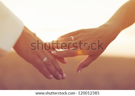 Wedding couple holding hands on sunset background - stock photo