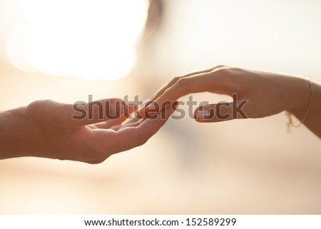 Wedding couple holding hands on sunset. Wedding rings. Man giving an engagement ring to his girlfriend - stock photo