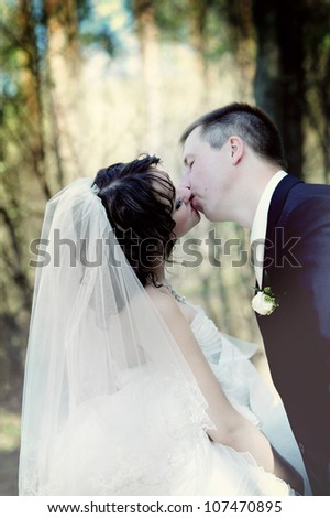 wedding couple hugging and kissing in a private moment of joy - stock photo