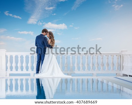Wedding couple hugging and standing with her back outdoors near the pool. Happy bride and groom in love on their honeymoon. Woman in an elegant dress a man in the suit.  - stock photo