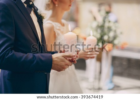 Wedding couple in church holding candles