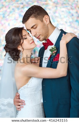 Wedding couple in love. Beautiful bride in white dress and veil with handsome groom in blue suite standing and embracing each other indoors against beautiful colored background bokeh like their dreams - stock photo