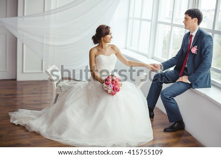 Wedding couple in love. Beautiful bride in white dress with brides bouquet and handsome groom in blue suite posing indoors in decorated studio room, white bright interior with big window. The husband - stock photo