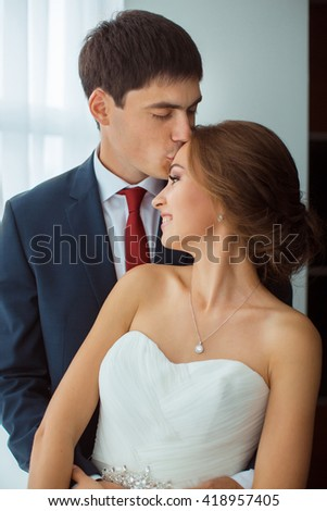 Wedding couple in love. Beautiful bride in white dress with brides bouquet and handsome groom in blue suit standing indoors at home, agaist window. Husband kissing and embracing his wife - stock photo