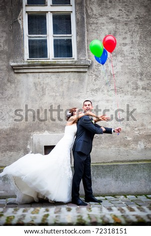 Wedding couple in love having fun. Groom is hiding the balloons from the bride - stock photo