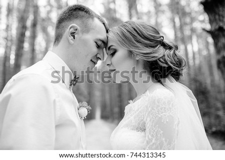 Wedding couple in the forest. Beautiful Bride and groom on a walk, look at each other. White wedding dress. Black and white photo