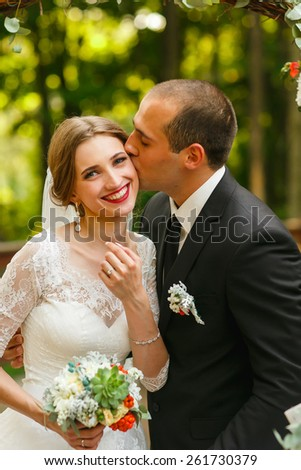 wedding couple in wood kissing