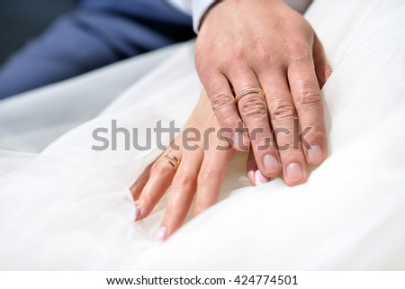 Wedding couple is holding hands. Beauty bride with groom. Beautiful model girl in white dress. Man in suit. Female and male portrait. Close-up woman's arms. Cute lady and guy indoors