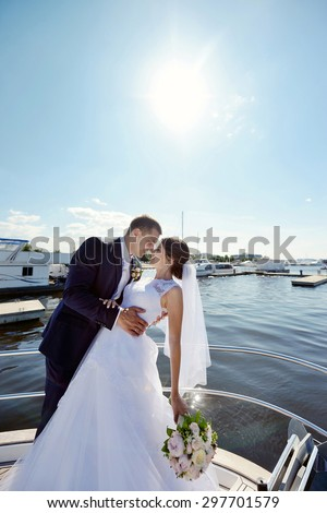 Wedding couple is hugging on a yacht. Beauty bride with groom. Beautiful model girl in white dress. Man in suit. Female and male portrait. Woman with lace veil. Cute lady and guy outdoors