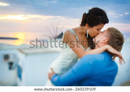 wedding couple kissing at sunset in Santorini - stock photo