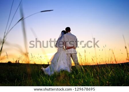 Wedding couple looking in mountain hill on sunset - stock photo