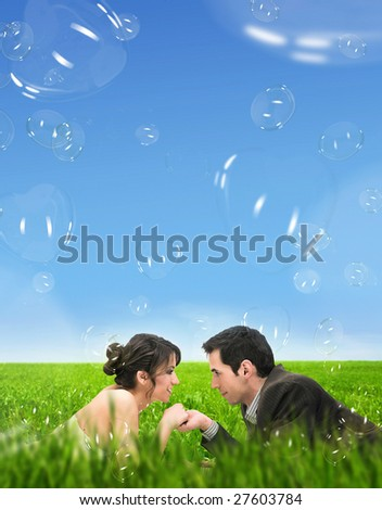 Wedding couple lying on summer meadow over romantic soap bubbles - stock photo
